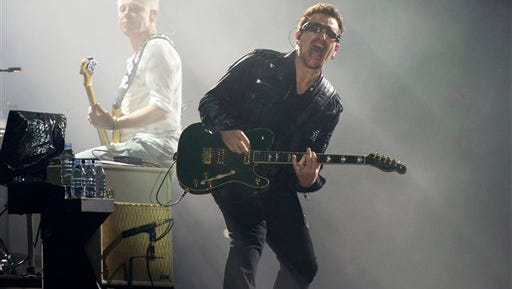 In this file photo, Bono, right, and Adam Clayton, from the rock group U2, perform in concert as part of U2's 360 Tour at the New Meadowlands Stadium in East Rutherford, N.J. Bono wrote on the band's website Thursday he may never play guitar again due to injuries suffered in a New York City cycling accident in November.