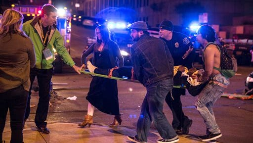 This file photo shows bystanders assisting first responders at the scene at SXSW festival in Austin, Texas, where 2 people died and dozens more were injured after a hit and run. The first wave of victim lawsuits since four people died at the South by Southwest music festival accused organizers  Dec. 18 of safety lapses after a driver smashed through a barricade and into a crowd of concertgoer's.