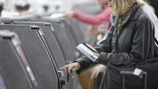 In this file photo, a traveler checks in for her flight at an American Airlines ticket kiosk at Lambert St. Louis International Airport in St. Louis. Thieves with stolen usernames and passwords have broken into customer accounts at American and United airlines and in some cases booked free trips, the airlines said today.