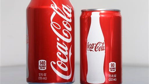 A 7.5-ounce can of Coca-cola, right, is posed next to a 12-ounce can for comparison Monday in Philadelphia. As people cut back on soda, the two beverage giants, Coke and Pepsi, are increasingly pushing smaller cans and bottles they say contain fewer calories and induce less guilt.