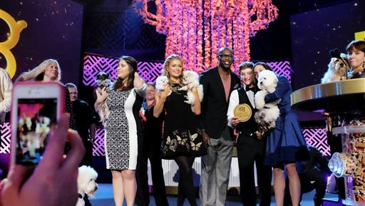 This Saturday, Jan. 10, 2015 photo Paris Hilton, center, joins former NFL player Terrill Owens with the other nominees on the stage during the taping of the 2015 World Dog Awards at the Barker Hanger in Santa Monica, Calif. The inaugural World Dog Awards hosted by comic George Lopez will air Jan. 15 on The CW Network. Canine winners, along with a few humans and a cat, will be presented with golden fire hydrant statuettes. (AP Photo/Richard Vogel)