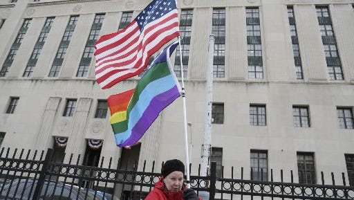 Cindy Clardy, 63, of Southfield waves her rainbow flag and American Flag across the street from the Theodore Levin Federal Court in Detroit as the trial to overturn the ban on gay marriage continued Tuesday Mar. 4, 2014.