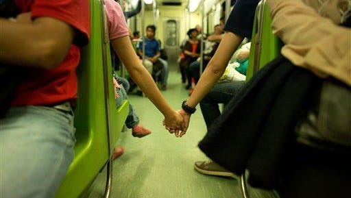 A young couple, unable to find seats together in the metro, hold hands across the aisle at the start of evening rush hour in Mexico City.