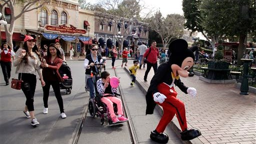 Visitors follow Mickey Mouse for photos at Disneyland, Thursday, Jan. 22, 2015, in Anaheim, Calif.  Seventy people have been infected in a measles outbreak that led California public health officials to urge those who haven't been vaccinated against the disease, including children too young to be immunized, should avoid Disney parks where the spread originated.  (AP Photo/Jae C. Hong)