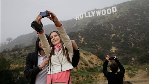 Brazilian tourists Marcela Lucato takes a selfie with husband, Junior, as their son, Mikhael, right, takes pictures of the Hollywood Sign Jan. 20  in Los Angeles. You can't quite touch the Hollywood sign, however, thanks to a protective fence, a bank of security cameras and the threat of arrest. But you can get close enough for a great photo, one of those comical poses where you pretend to be holding it aloft like Atlas carrying the world on his shoulders.