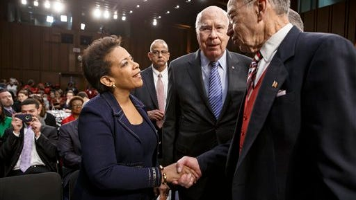 Attorney general nominee Loretta Lynch greets Sen. Charles Grassley, R-Iowa, right, chairman of the Senate Judiciary Committee, and  Sen. Patrick Leahy, D-Vt., in Washington on Wednesday, Jan. 28, 2015, before her confirmation hearing before the committee.