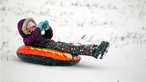 Zoey Littmann, 7, of Milwaukee, records herself sliding down a hill at Hartung Park in Wauwatosa on Sunday, Feb. 1, 2015.
