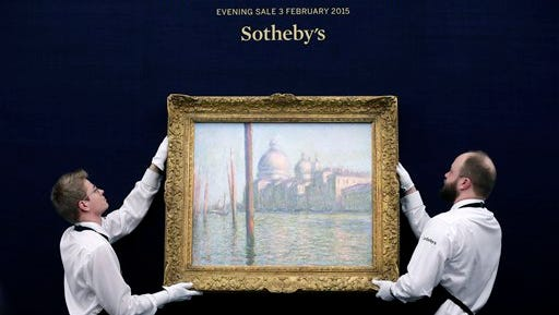 """In this file photo, Sotheby's staff pose for a picture with 'Le Grand Canal' by Claude Monet, during a preview of their upcoming Impressionist and Modern, Surrealist and Contemporary Art sale, at the auction house in London, England. """"Le Grand Canal,"""" fetched 23.7 million pounds ($35.6 million) at Sotheby's, though it didn't reach the top of its pre-sale estimate of 20 million pounds to 30 million pounds. The Impressionist, Modern and Surrealist auction on Tuesday raised 186.4 million pounds ($280.2 million), the highest-ever total for a single sale in London."""
