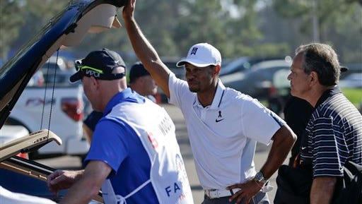 Tiger Woods, center, loads his car after withdrawing during the first round of the Farmers Insurance Open golf tournament Thursday, Feb. 5, 2015, in San Diego. (AP Photo/Gregory Bull)