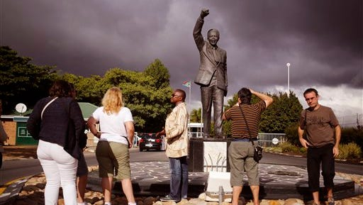 A tour guide,speaks to French tourists beside the statue of former South African President Nelson Mandela near the town of Franschhoek, South Africa,