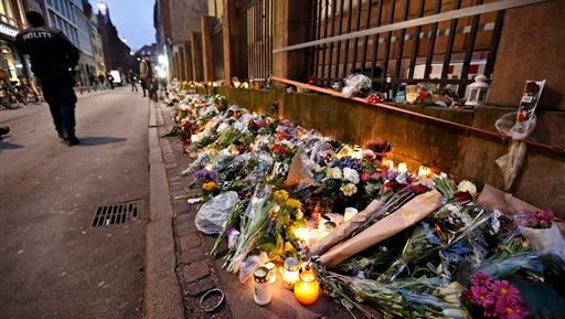 Flowers and candles lay in front of the Jewish Synagogue, in Copenhagen, Monday, Feb. 16, 2015, following the attacks at the weekend. One person was killed and two policemen wounded  in front of the Synagogue in Copenhagen. Danish police shot and killed a man early Sunday suspected of carrying out shooting attacks at a free speech event and then at a Copenhagen synagogue, killing a Danish documentary filmmaker and a member of the Scandinavian country's Jewish community. Five police officers were also wounded in the attacks. (AP Photo/Polfoto, Jens Dresling)  DENMARK OUT