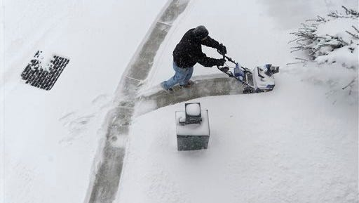 Building manager Mike Long uses an electric snowblower to clear walkways outside the Wantz Building in Westminster, Md. as snow falls Saturday, Feb. 21, 2015. (AP Photo/Carroll County Times, Dylan Slagle)