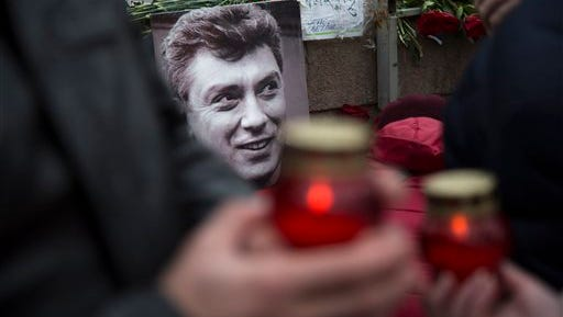 Mourners following the Russian tradition of memorialising a person nine days after a death lay flowers and votive candles at the place where Boris Nemtsov, a charismatic Russian opposition leader and sharp critic of President Vladimir Putin, was gunned down on Friday, Feb. 27, 2015 near the Kremlin, in Moscow, on Saturday, March 7, 2015.  Two suspects have been detained in the killing a week ago of opposition politician Boris Nemtsov, the head of Russia's federal security service said Saturday, an announcement received with both skepticism and reserved satisfaction by some of Nemtsov's comrades.(AP Photo/Alexander Zemlianichenko)