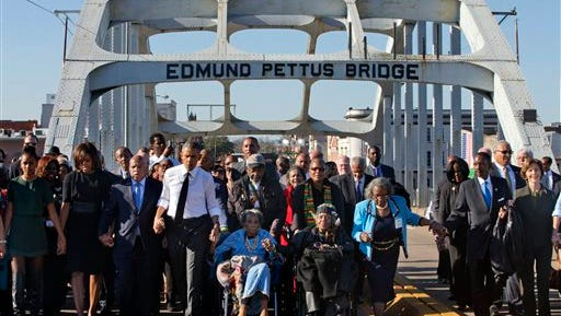 """President Barack Obama, fourth from left, walks holding hands with Amelia Boynton Robinson, who was beaten during """"Bloody Sunday,"""" as they and the first family and others including Rep. John Lewis, D-Ga, left of Obama, walk across the Edmund Pettus Bridge in Selma, Ala,. for the 50th anniversary of the landmark event of the civil rights movement, Saturday, March 7, 2015. At far left is Sasha Obama and at far right is former first lady Laura Bush. Adelaide Sanford also sits in a wheelchair."""