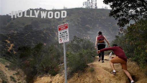 This Jan. 20, 2015 file photo shows two tourists walking up the dirt trail past a no hiking sign to get closer to the Hollywood Sign in Los Angeles. Like pilgrims flocking to a holy shrine, they come from all over the world to pay homage, not to a deity but to something similar - the people they see on TV and in the movies. They are the seekers of the Hollywood Sign, that symbol of the Land of the Rich and Famous. And just like those on pilgrimages to St. Peter's Basilica in Rome or the Acropolis in Greece, they press to get just as close as they can to the immortality the symbol represents.