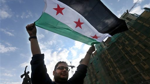 An anti-Syrian government protester waves the Syrian revolutionary flag during a protest to mark the 4th anniversary of the Syrian uprising, at the Martyrs square in downtown Beirut, Lebanon, Sunday, March 15, 2015. Before the civil war started in March 2011, an estimated 22 million people lived in Syria. More than 3.8 million Syrians have fled their country in the four years since the uprising against President Bashar Assad began. (AP Photo/Hussein Malla)