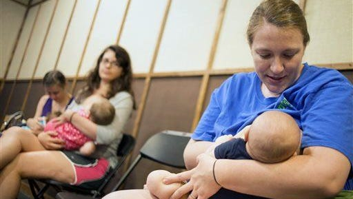 Erin Bolton feeds her 9-month-old Parker during the Global Big Latch On breastfeeding awareness event on Friday, Aug. 1, 2014, in Auburn, Ala.  A Brazilian study links breastfeeding to higher earnings and IQ.