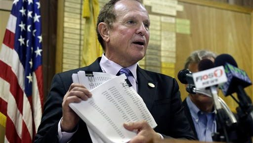 New Jersey Sen. Raymond J. Lesniak, D- Elizabeth, N.J., holds up petitions with over 15,000 signatures against New Jersey Gov. Chris Christie's announced settlement with Exxon Mobil Corp., Tuesday, April 7, 2015, in Linden, N.J. Lesniak called the Christie administration's proposed $225 million settlement of New Jersey's $8.9 billion claim for restoration of damage and destruction in the areas of Exxon Mobil's refineries in Linden, Bayonne and other facilities, the biggest corporate giveaway in New Jersey history. (AP Photo/Mel Evans)