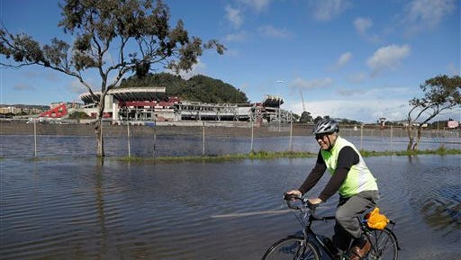 A man rides his bicycle around a flooded section of roadway as demolition continues in the background at Candlestick Park Tuesday, April 7, 2015, in San Francisco. An unusually cold spring storm brought heavy rain and hail to parts of Northern California on Tuesday and coated the mountains in snow, a welcome respite that will do little to ease the historic drought, forecasters say. Candlestick Park is being demolished so houses, a hotel and a shopping center can be built on the site of the former home of the San Francisco Giants baseball team and 49ers football team. (AP Photo/Eric Risberg)