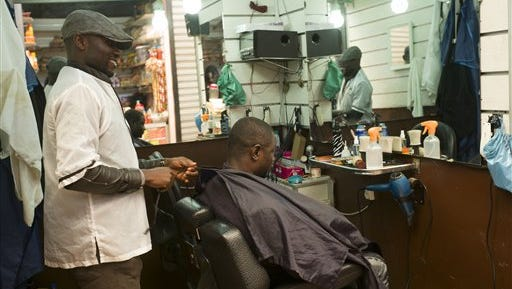 In this photo taken Tuesday, Feb. 24, 2015  African refugee John Pessima, left, from Sierra Leone, works in his hairdressing salon in the Senegalese souk of Casablanca, Morocco. Over the past year, Morocco has been working to grant legal status to the tens of thousands of immigrants living in the country to give them an opportunity to settle and take advantage of the health and education system. Part of this program announced on Feb. 9 is to aid the immigrants start small businesses. (AP Photo/Abdeljalil Bounhar)