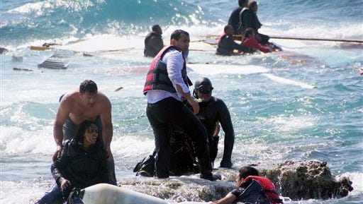 A man rescues an migrant from the Aegean sea, off  the Greek island of Rhodes, on Monday, April 20, 2015. Greek authorities said that at least three people have died, including a child, and more than 90 were saved after a wooden boat carrying migrants ran aground.