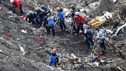 FILE - In this March 26, 2015 file photo, rescue workers work on debris of the Germanwings jet at the crash site near Seyne-les-Alpes, France. The co-pilot of Germanwings Flight 4525 tried a controlled descent on the previous flight that morning to Barcelona before the plane crashed into a mountainside in March on its way back to Germany, French air accident investigators said in a new report released Wednesday May, 6, 2015. (AP Photo/Laurent Cipriani, File)