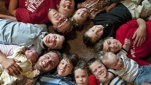 In this Aug. 6, 2013 photo, the 12 Schwandt brothers pose for a photograph in their home in Rockford, Mich. Clockwise from bottom left are: Tyler, 21, holding Tucker, 2 days;  Vinny, 10; Drew, 16; Zach, 17; Charlie, 3; Calvin, 8; Brandon, 14; Luke, 19 months; Gabe, 6; Wesley, 5 and Tommy, 11. Parents Jay and Kateri Schwandt are expecting a baby on Saturday, May 9, 2015, a day before Mother's Day, and they're sticking to their tradition of not finding out in advance whether they're having a boy or girl.