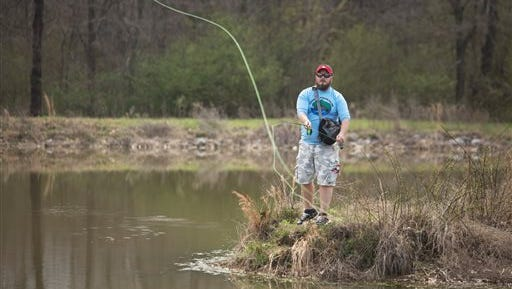 In this March 31, 2015 photo, U.S. Army veteran Paul Holcomb fly fishes at Beaver Lake in Shelby Farms in Memphis, Tenn. Holcomb has been a participant in Project Healing Waters, a recreational therapy program associated with the VA.