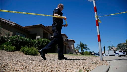 A Phoenix Police Department officers attaches police tape creating a cordon near a home Friday, April 17, 2015, in Phoenix, the day after five people were killed inside after a shooting in that same house.  Phoenix police said Friday that a man who had been in a business dispute with his two brothers shot and killed them, his mother and one of their wives before taking his own life.  (AP Photo/Ross D. Franklin)