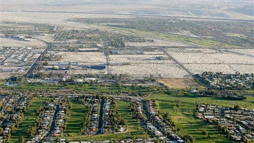 FILE - In this April 3, 2015 aerial file photo, lush green golf courses border the edge of the desert in Palm Springs, Calif.  Pressed by the fourth year of bone-dry weather and the threat of state-mandated water cuts, some of the poshest courses in California are ceding back to nature some of their manicured green, installing high-tech moisture monitoring systems and letting the turf they don't rip up turn just a little bit brown. (AP Photo/Chris Carlson, File)