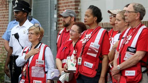 "Police officers and members of the Red Cross listen during a service of reflection on Sunday May 17, 2015, in Philadelphia, near the site of an Amtrak train derailment. The U.S. passenger train operator Amtrak will resume full service in the Northeast Corridor on Monday in ""complete compliance"" with federal safety orders following last week's deadly derailment, officials announced Sunday."
