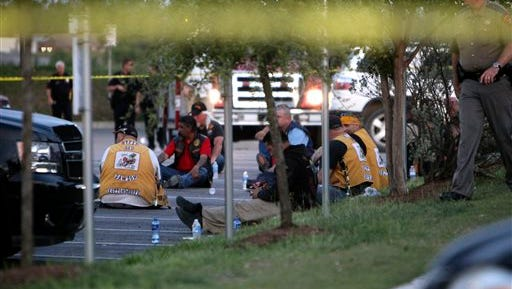 Police detain and watch members of various motorcycle clubs outside the Twin Peaks restaurant in Waco, Texas, Sunday, May 17, 2015. A shootout among rival motorcycle gangs at a popular Texas restaurant left nine bikers dead and more than a dozen injured, a police spokesman said Sunday.