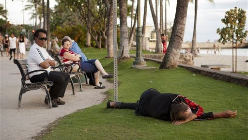 FILE - In this May 13, 2011, file photo, tourists watch the sunset as a man sleeps on the grass near Waikiki Beach in Honolulu. Honolulu Mayor Kirk Caldwell has vetoed a bill that would have expanded the city's ban on sitting and lying down on sidewalks. Caldwell said Thursday, May 21, 2015, that the city would face legal challenges if he signed Bill 6 into law. His administration is proposing an alternative that he says the city can defend. (AP Photo/Marco Garcia, File)