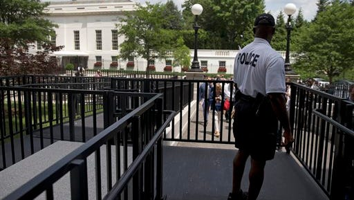 A member of the Secret Service Police looks toward the West Wing of the White House in Washington, Tuesday, June 9, 2015, during an evacuation of the media area of the White House because of a bon threat. Part of the White House was evacuated amid security concerns. Secret Service officers interrupted a live, televised press briefing with the White House press secretary on Tuesday and evacuated the James S. Brady Briefing Room shortly after 2 p.m. The officers would not say what prompted the evacuation, and the White House had no immediate information about the incident.
