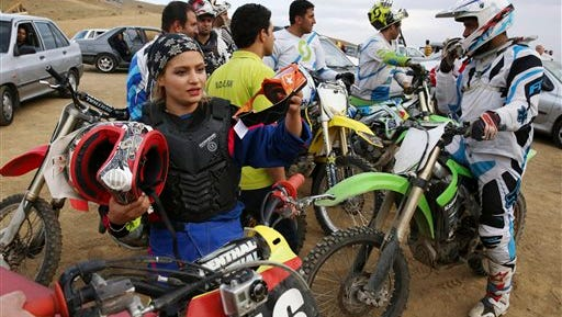 """In this photo taken Friday, June 5, 2015, Iranian motocross rider Behnaz Shafiei, left, prepares for a training session, standing by other riders at a racetrack near the village of Baraghan, some 19 miles (30 kilometers) west of the capital Tehran, Iran. """"When two days pass and I do not ride my motorcycle, I get really ill. Even the thought of not having a motorcycle some day gives me an awful feeling,"""" Shafiei said. (AP Photo/Vahid Salemi)"""