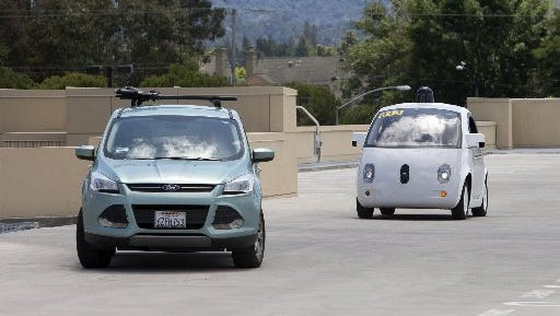 A two-seater prototype of Google's self-driving car, left, slows down as a SUV crosses its path during a demonstration at Google on May 13, 2015 in Mountain View, Calif.