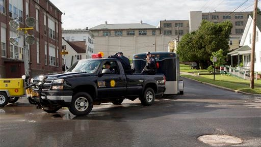 Corrections officers ride in a truck, Tuesday, June 16, 2015, in Dannemora, N.Y. as they pass the manhole cover that prisoners used 11 days earlier as part of their escape route from the Clinton Correctional Facility, rear. The 11th day of searching began Tuesday with roadblocks still in place. (AP Photo/Mark Lennihan)