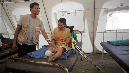 In this June 10, 2015 photo, a physiotherapist attends to  45-year-old Pemba Tamang, who had his right foot amputated after it was injured in the quake as he lies at the Trishuli District Hospital, about 80 kilometers (50 miles) northwest of Kathmandu, Nepal. Many people with orthopedic injuries are still coming in for treatment in this hard-hit area where staff are working out of tents because of damage to the hospital buildings. (AP Photo/Niranjan Shrestha)