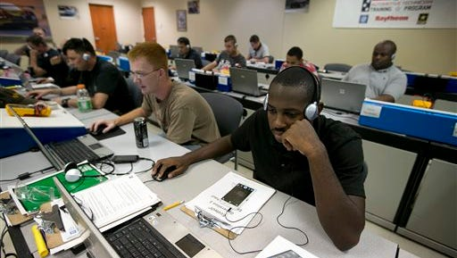 In this Thursday, June 18, 2015, photo, Spc. Yahshem Hicks, right, and Spc. Anthony Young take part in a computer training class at Fort Hood, Texas. The men are participants in Shifting Gears, a program sponsored by General Motors that teaches automotive skills and tries to match participants with dealerships around the country. The U.S. Labor Department reports on the number of people who applied for unemployment benefits during the week ending June 20 on Thursday, June 25, 2015. (Deborah Cannon/Austin American-Statesman via AP)
