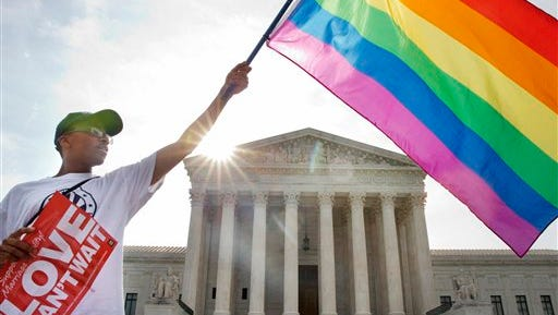 Carlos McKnight of Washington waves a flag in support of gay marriage outside of the Supreme Court in Washington, Friday