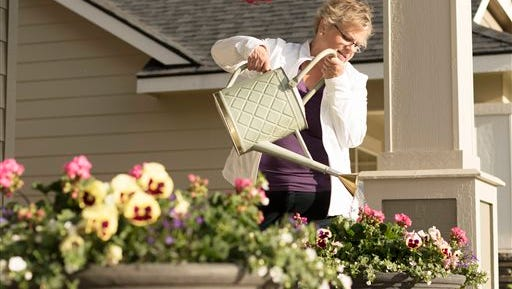 Amy Shives waters her flowers at her house, Wednesday, June 3, 2015, in Spokane, Wash. Shives was diagnosed with early onset Alzheimer's disease in 2011 and has since been involved with the Alzheimer's Association. Nearly two-thirds of Americans with Alzheimer's disease are women, and now some scientists are questioning the long-held assumption that it's just because women tend to live longer than men.