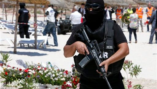 A hooded Tunisian police officer stands guard ahead of the visit of top security officials of Britain, France, Germany and Belgium at the scene of Friday's shooting attack in front of the Imperial Marhaba hotel in the Mediterranean resort of Sousse, Tunisa, Monday, June 29, 2015. The top security officials of Britain, France, Germany and Belgium are paying homage to the people killed in the terrorist attack on Friday.