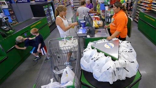 In this June 4, 2015 photo, a customer, center, checks out at a Wal-Mart Neighborhood Market store in Bentonville, Ark. The Commerce Department releases retail sales data for June on Tuesday, July 14, 2015. (AP Photo/Danny Johnston)