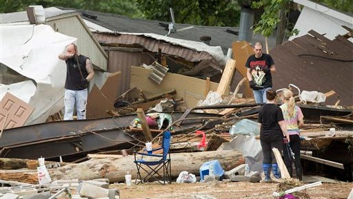 Residents of a mobile home park look for belongings after deadly flooding in Flat Gap, Ky., Tuesday, July 14, 2015. Flash floods in northern Johnson County outside of Paintsville destroyed homes and vehicles and residents were reported missing a day after the floods. (AP Photo/David Stephenson)
