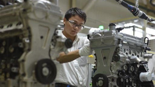 A worker assembles engines at the General Motors engine plant in Wuhan in central China's Hubei province. General Motors and other automakers are cutting prices of some models as they try to maintain the same sales they reported in 2014, despite volatility in the country's stock market.