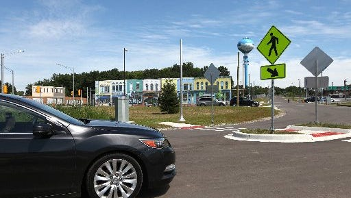 Movable building facades are seen as a car drives on the testing road at Mcity on the grounds of the University of Michigan in Ann Arbor Monday.