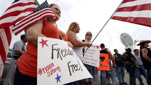 Christy Tucker, from left, Morgan Mason and Lauren Lindsey wave flags and signs on Monday, July 20, 2015, in front of the Lee Highway memorial set up for last Thursday's Chattanooga, Tenn., shooting victims. Muhammad Youssef Abdulazeez attacked two military facilities on Thursday, in a shooting rampage that killed several. (Dan Henry/Chattanooga Times Free Press via AP)