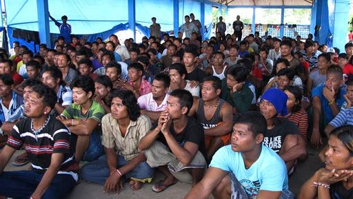 In this April 20, 2015, photo, former fishing slaves who were rescued from Indonesia's remote island village of Benjina gather at a temporary government-run shelter on the island of Tual, Indonesia. Hundreds of men remain unaccounted for and are believed to be fishing in Papua New Guinea.