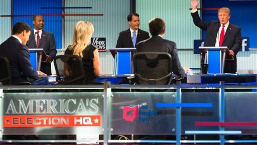 Republican presidential candidate Donald Trump, right, speaks to moderators from left foreground, Bret Baier, Megyn Kelly and Chris Wallace during the first Republican presidential debate at the Quicken Loans Arena Thursday, Aug. 6, 2015, in Cleveland. (AP Photo/John Minchillo)