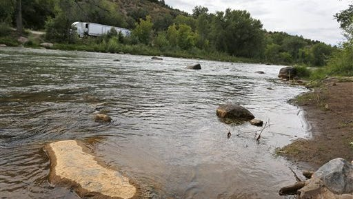 Dried yellow residue remains on a rock in the now-closed Animas River due to the Gold King mine chemical spill, downstream from the mine, in Durango, Colo., Tuesday, Aug. 11, 2015. The EPA took full responsibility Tuesday for the mine waste spoiling rivers downstream from Silverton, Colorado, but people who live near the idled and leaking Gold King mine say local authorities and mining companies spent decades spurning federal cleanup help. (AP Photo/Brennan Linsley)